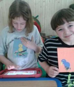 Photo of a girl working on a tablet and a boy proudly displaying his artwork, both patients at Nature's Edge Therapy Center in Rice Lake, WI.