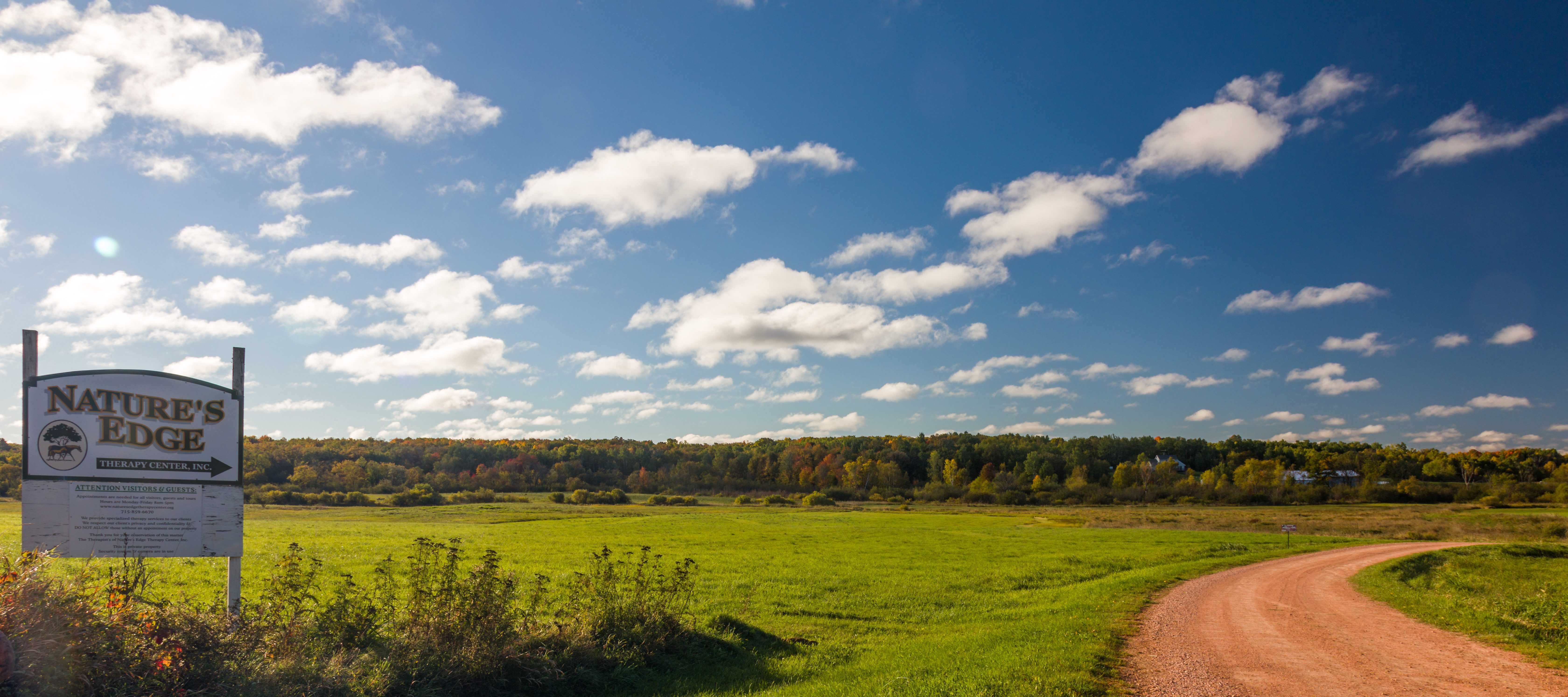 A shot of blue skies, a winding dirt road, and a white sign that says 'Nature's Edge Therapy Center, I nc.'